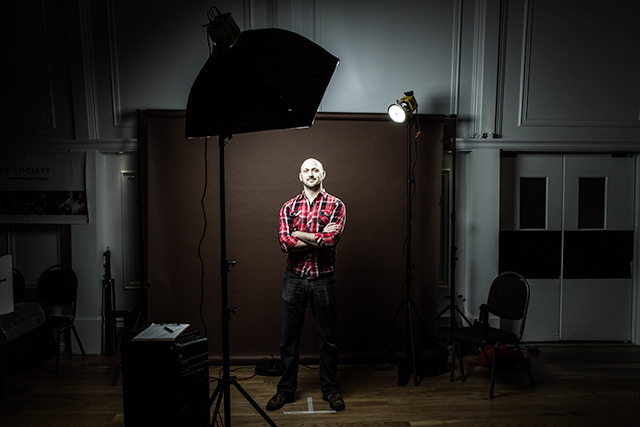 Vancouver photographer, Trevor Jansen, stands in front of his photo gear