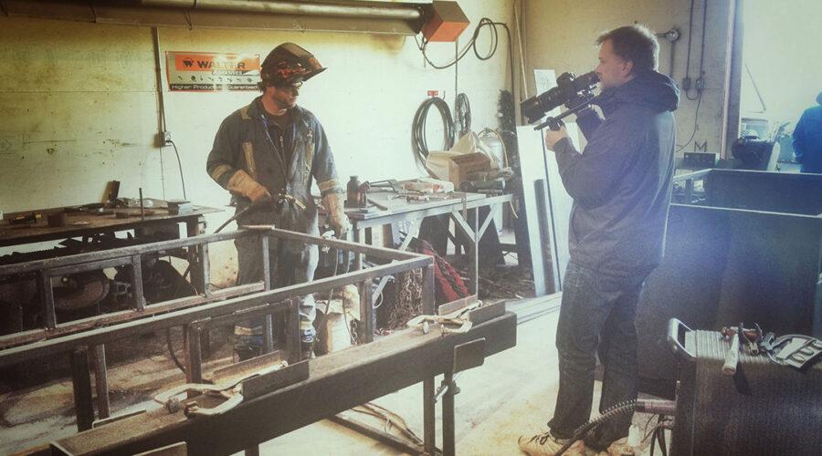 Videographer films a wielder in his shop