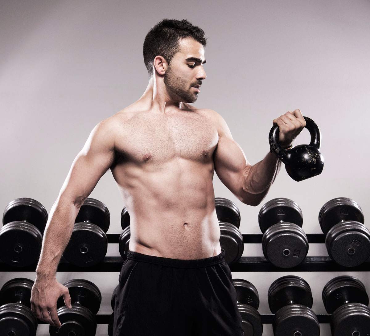 West Coast Fitness instructor demonstrates arm curls with a kettle bell | Commercial Photography
