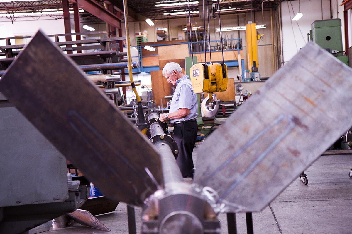 Commercial Photography for Dynamix Agitators Inc. | An engineer inspects an impeller shaft