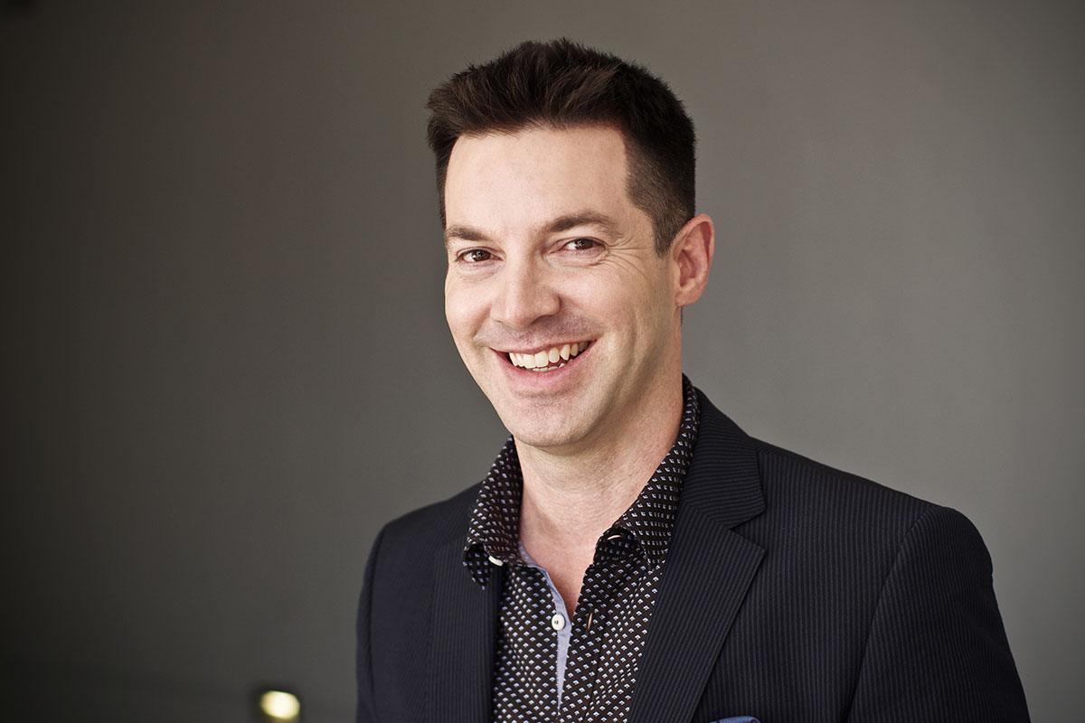 Business headshot of a smiling man